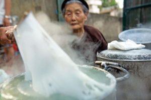 Một cụ bà đang làm bánh cuốn theo công thức truyền thống