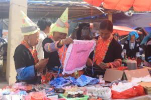 Những phụ nữ Dao bên món hàng mình ưng ý, có lễ bà ấy đang chuẩn bị mua