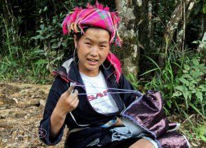 Một phụ nữ Nà Luồng đang may quần áo cho gia đình