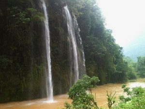 Nhìn từ trên cao, dòng thác Nặm Rứt đổ xuống như dòng mua, nước tung lên giữa ánh nắng lấp lánh cầu vồng